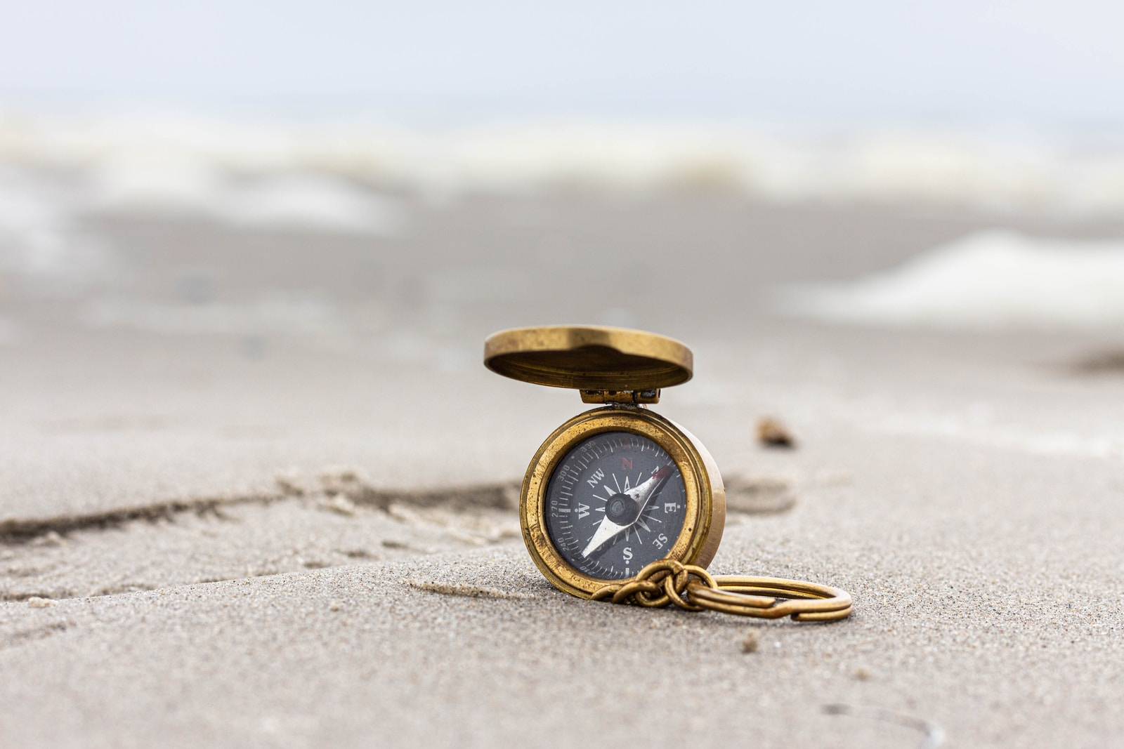 gold pocket watch on beach